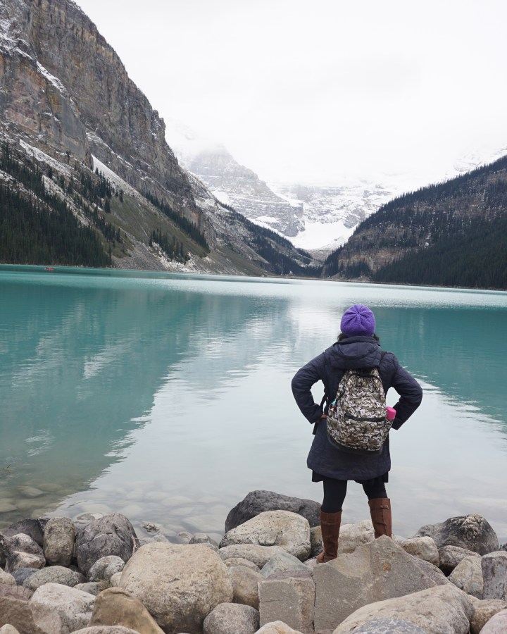 woman looking back towards mountain and lake