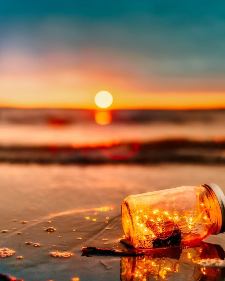 mason jar bottle with string lights by the seaside
