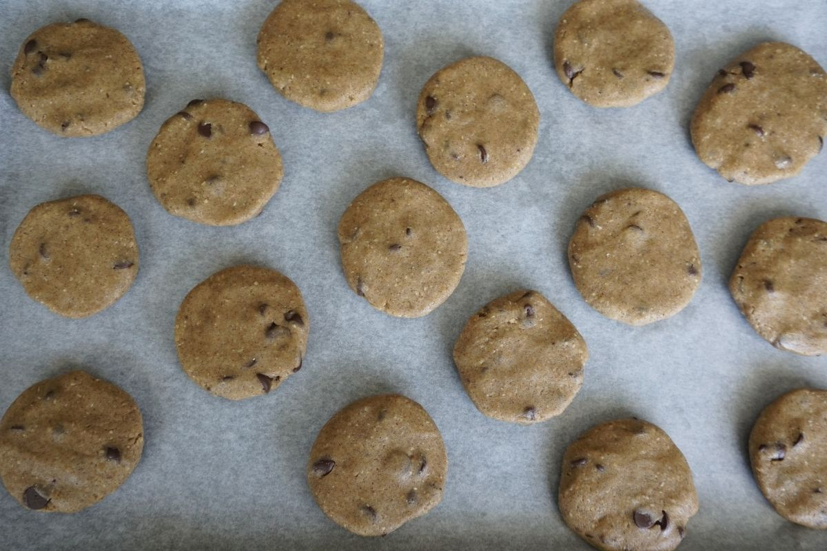 rolled and flattened cookies on parchment paper