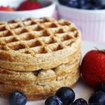 Stack of banana oatmeal waffles with fruits by the side