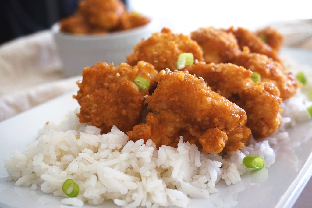 general tso cauliflower with rice on plate