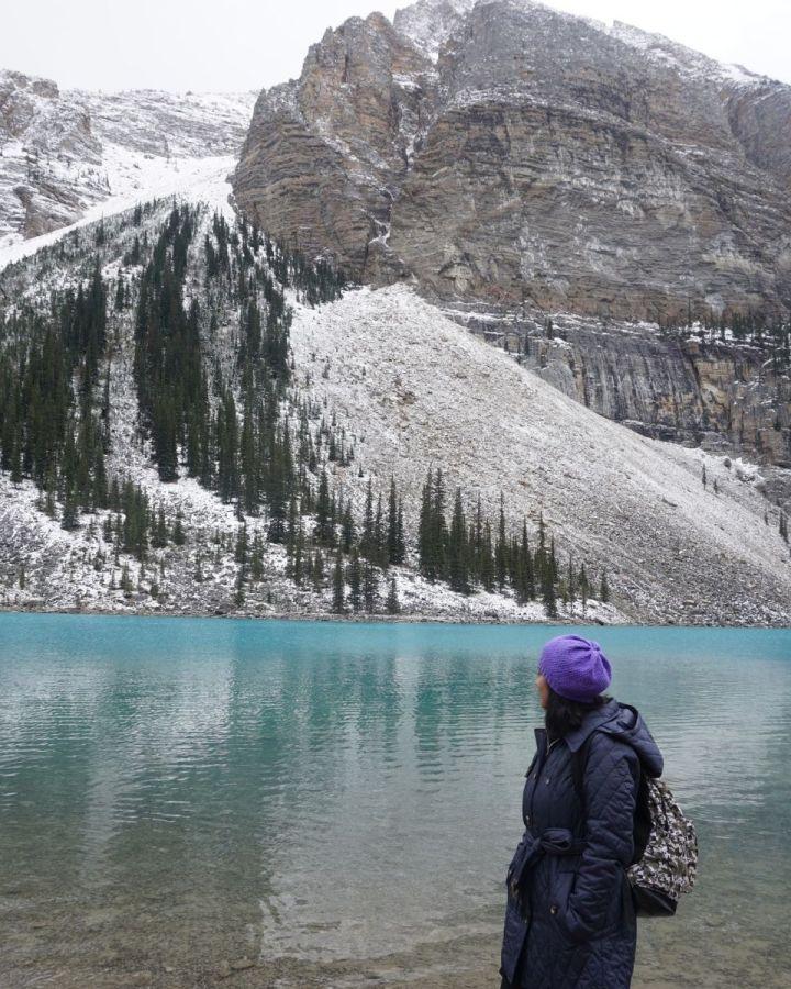 woman looking towards mountain beside a lake