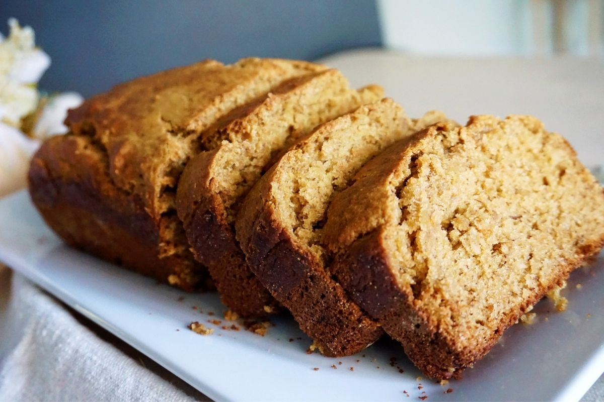banana bread with slices on a white plate