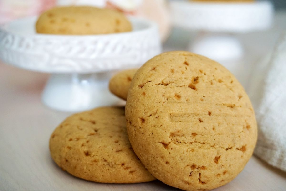 Wheat jaggery cookies and one cookie on the white stand.