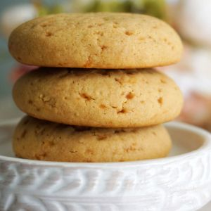Three cookies stacked on a white plate.