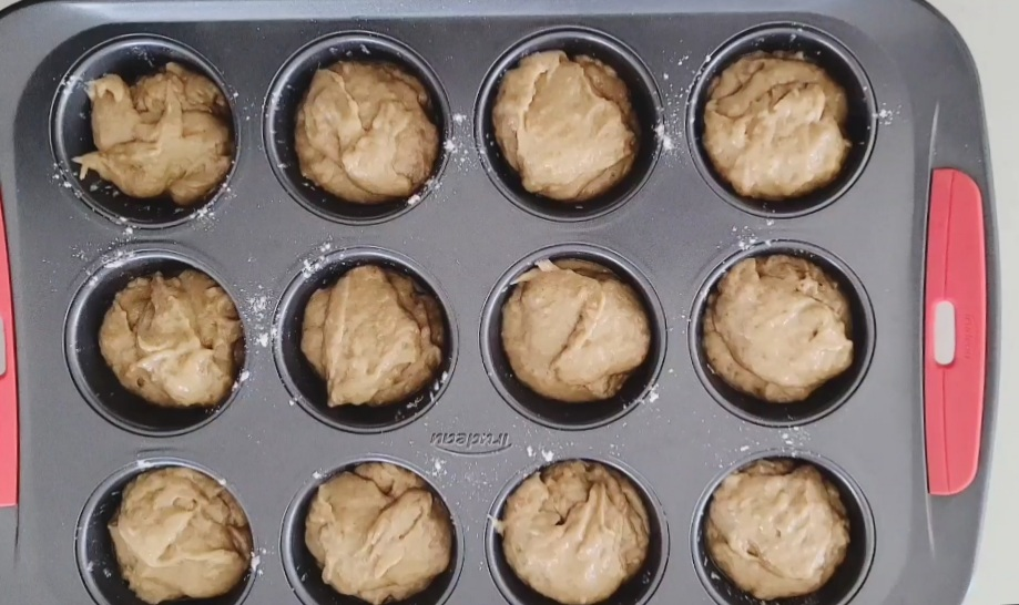 Batter added to muffin tray.