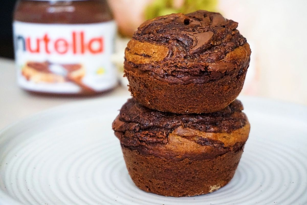 Stacked nutella swirled banana muffins on a white plate.
