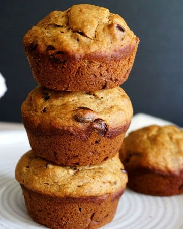 Three eggless muffins stacked and another one on a white plate.